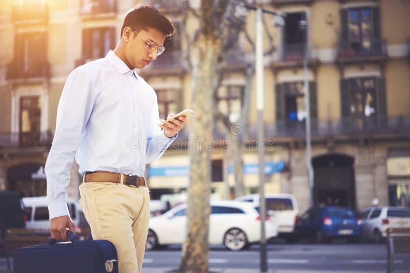 Geconcentreerde jonge zakenman die met aktentas het financiële nieuws lopen lezen royalty-vrije stock foto
