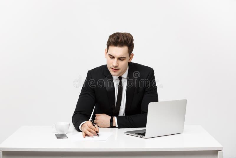 Geconcentreerde jonge zakenman het schrijven documenten bij bureau stock afbeelding
