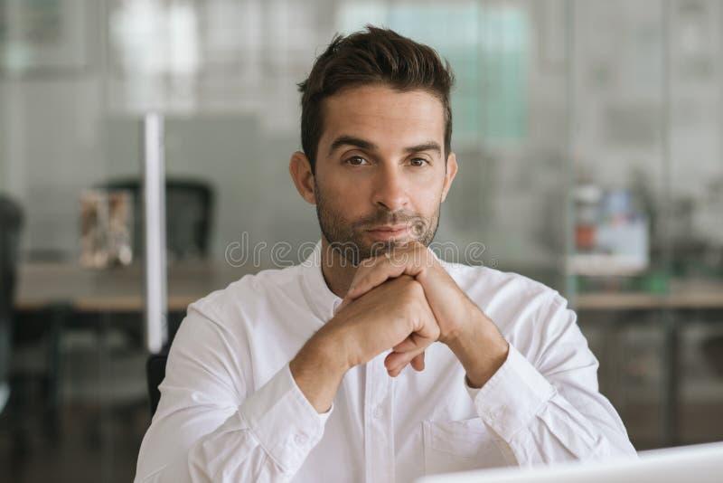 Geconcentreerde jonge zakenmanzitting alleen in een modern bureau stock fotografie