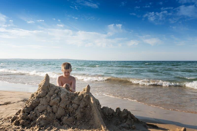 Geconcentreerde jongen die groot geel zandkasteel bouwen stock foto's