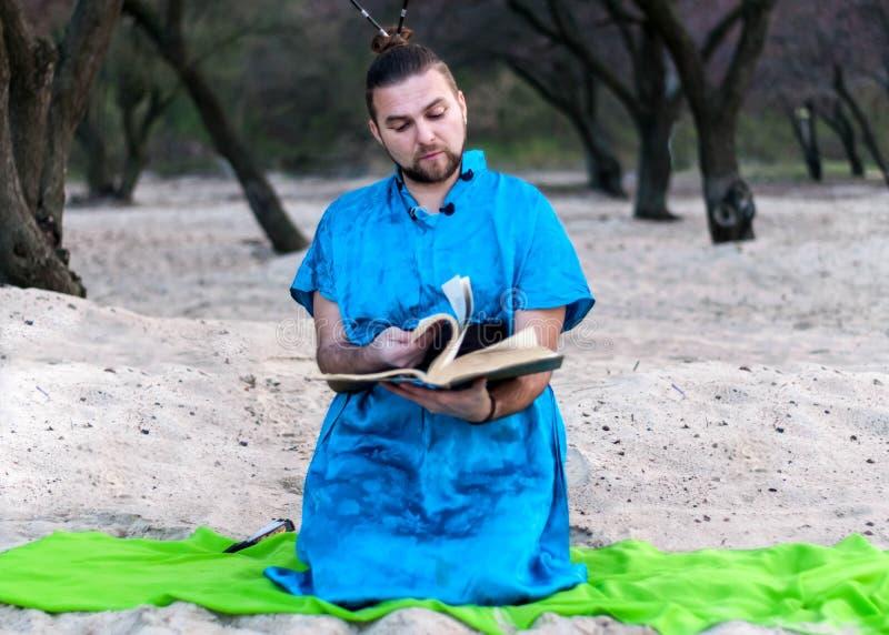 Geconcentreerde knappe gebaarde mens in blauwe kimonozitting die, die groot boek doorbladert en op zandig strand leest royalty-vrije stock foto's