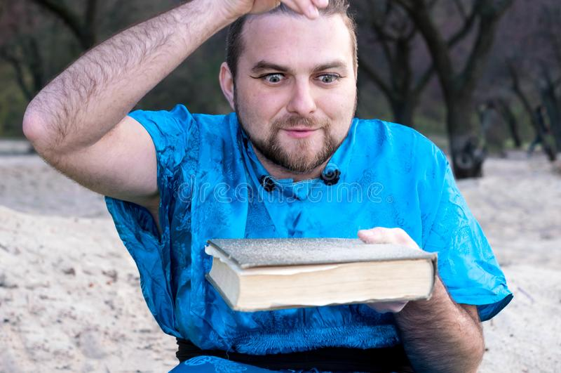 Geconcentreerde knappe mens in blauw kimono gietend zand op boek stock foto's