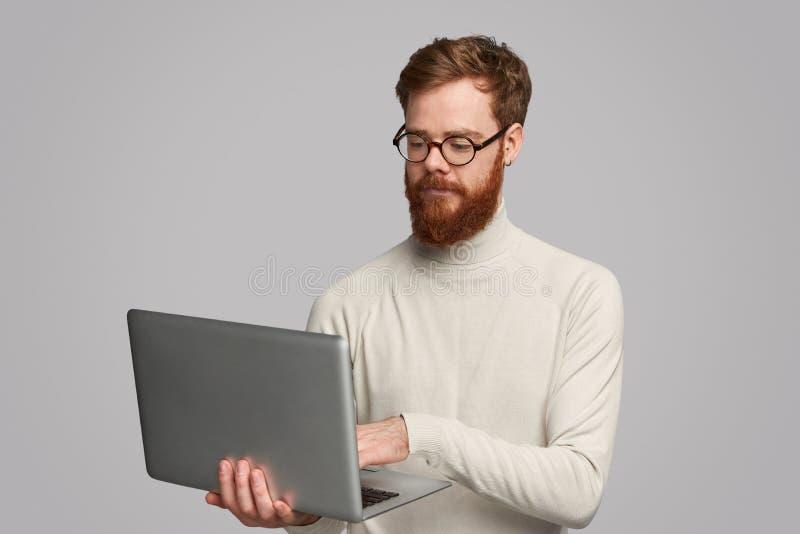 Geconcentreerde knappe mens die laptop met behulp van royalty-vrije stock foto's