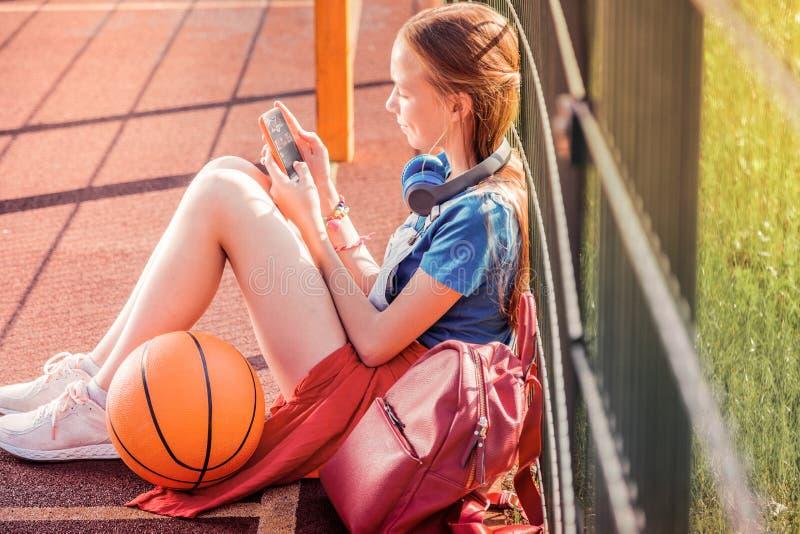 Geconcentreerde langharige meisjeszitting op een basketbalspeelplaats royalty-vrije stock afbeelding