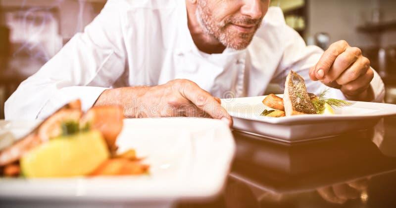 Geconcentreerde mannelijke chef-kok die voedsel in keuken versieren stock afbeelding