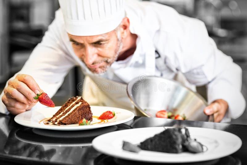 Geconcentreerde mannelijke gebakjechef-kok die desserts verfraaien royalty-vrije stock foto