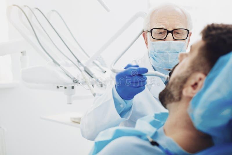 Geconcentreerde mannelijke tandarts die cariës verwijderen royalty-vrije stock foto