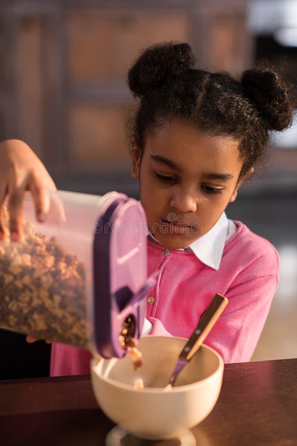 Geconcentreerde meisje het vullen kom met vlokken bij ontbijt stock afbeeldingen