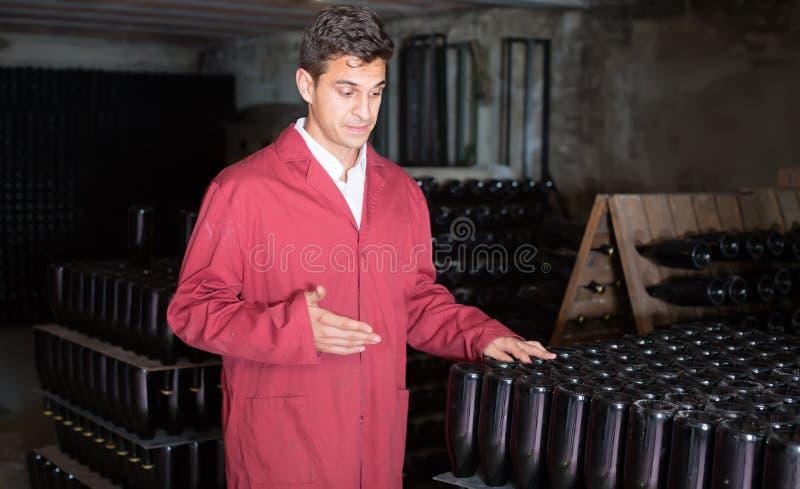 Geconcentreerde mens die het eenvormige werken met flessenopslag rac dragen stock foto's