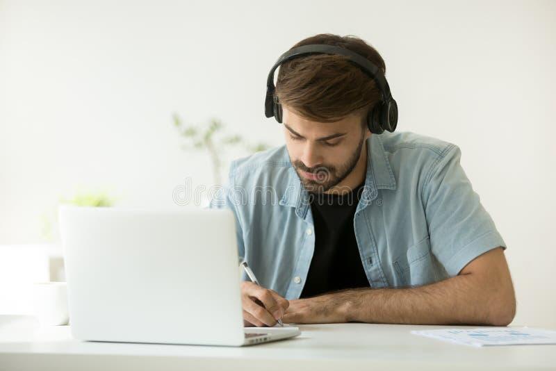 Geconcentreerde mens die hoofdtelefoons dragen die nota's schrijven die online verstand leren royalty-vrije stock afbeelding