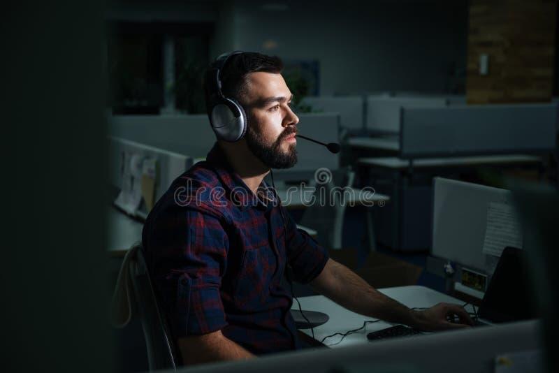Geconcentreerde mens in hoofdtelefoons die op nacht donker kantoor werken royalty-vrije stock foto's