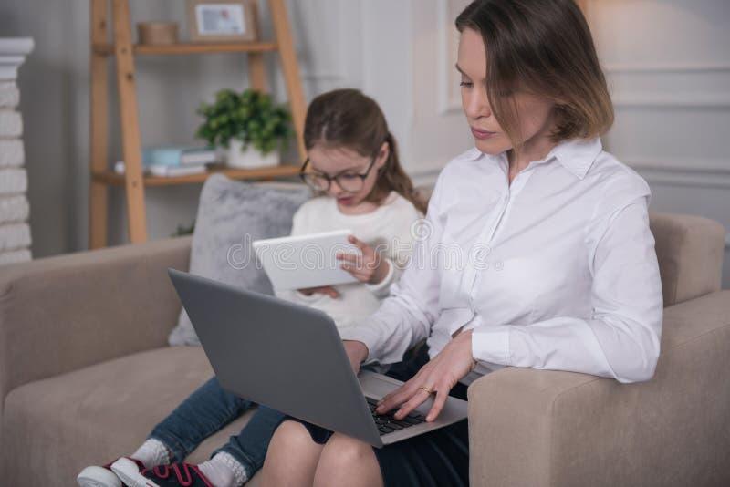 Geconcentreerde moeder die aan haar laptop werken stock afbeeldingen