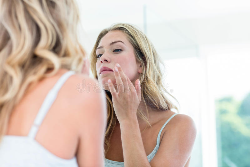 Geconcentreerde mooie jonge vrouw die zich in de badkamersspiegel bekijken royalty-vrije stock afbeelding