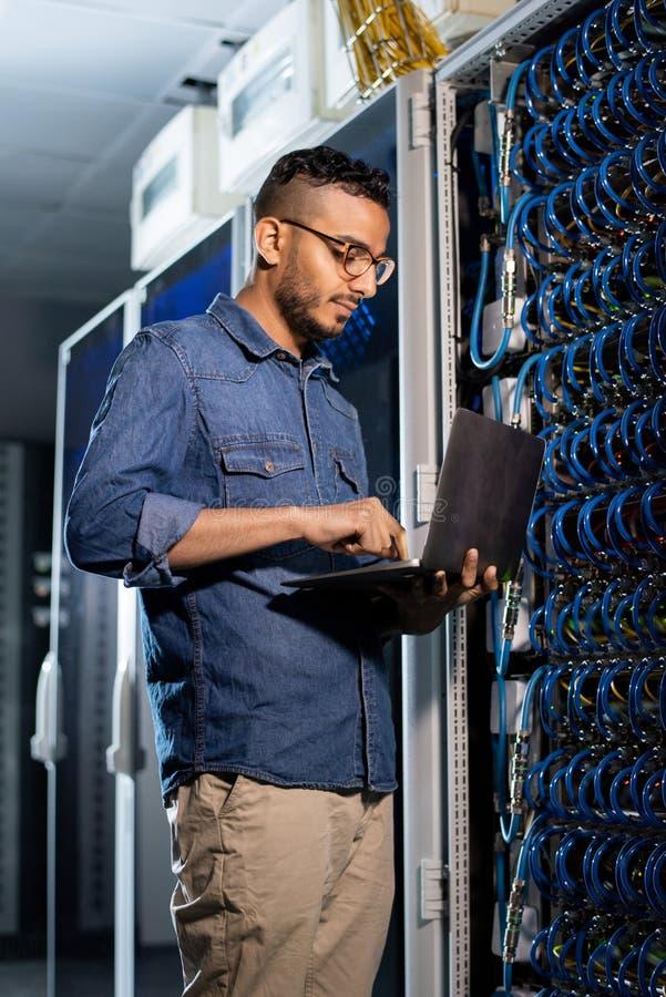 Geconcentreerde netwerkingenieur die databaseserver onderzoeken stock afbeelding