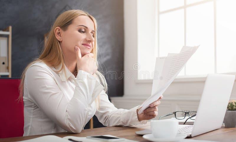 Geconcentreerde onderneemster die documenten controleren op kantoor stock afbeelding