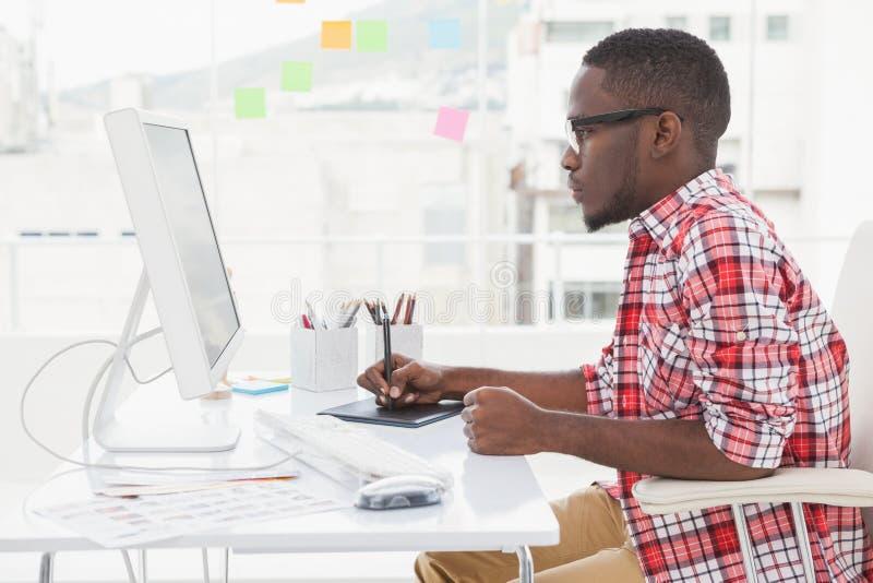 Geconcentreerde ontwerper die becijferaar en computer met behulp van royalty-vrije stock afbeelding