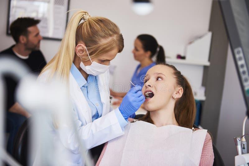 Geconcentreerde orthodontist die tandspiegel gebruiken royalty-vrije stock afbeeldingen