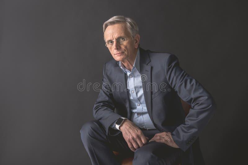 Geconcentreerde oude zakenman plaatsbepaling op zetel stock foto