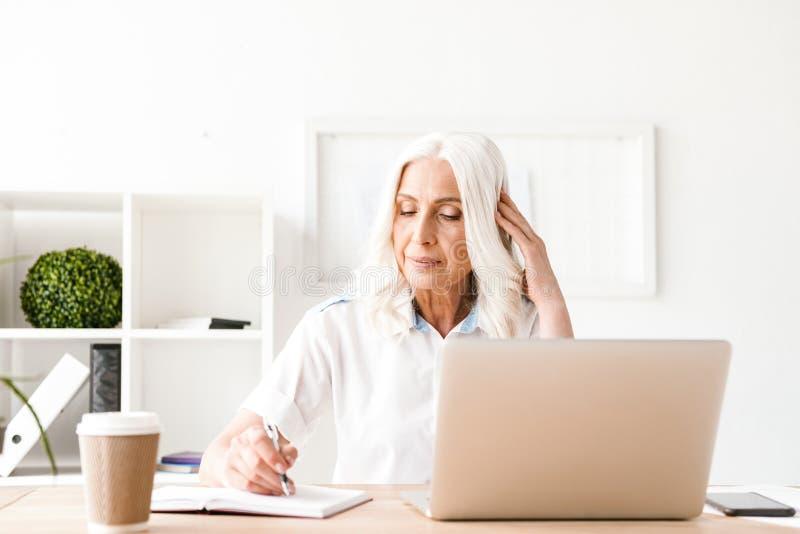 Geconcentreerde rijpe vrouw met laptop computer stock afbeeldingen