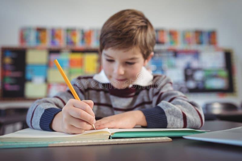 Geconcentreerde schooljongen die in klaslokaal bestuderen stock afbeeldingen