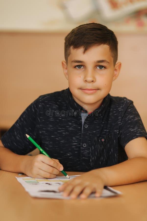 Geconcentreerde schooljongenzitting bij bureau en het schrijven in oefenboek royalty-vrije stock afbeelding