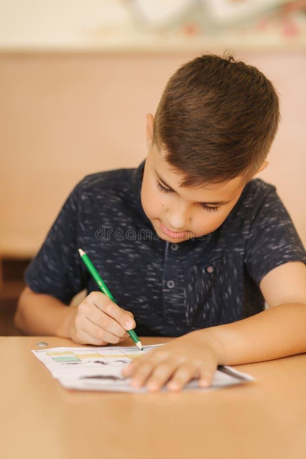 Geconcentreerde schooljongenzitting bij bureau en het schrijven in oefenboek stock foto's