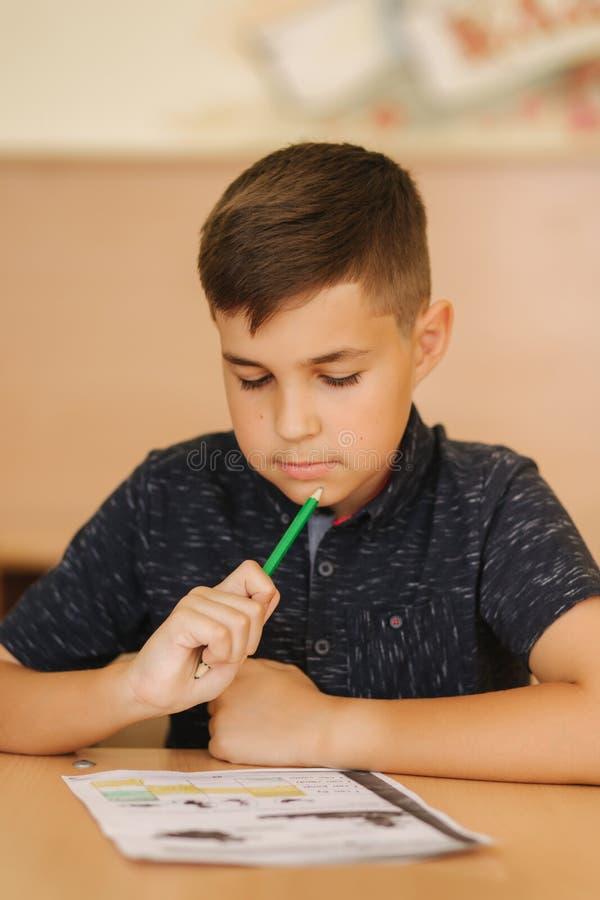 Geconcentreerde schooljongenzitting bij bureau en het schrijven in oefenboek stock fotografie