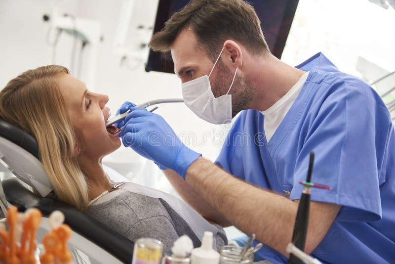 Geconcentreerde stomatologist die tandboor en tandspiegel gebruiken royalty-vrije stock afbeeldingen