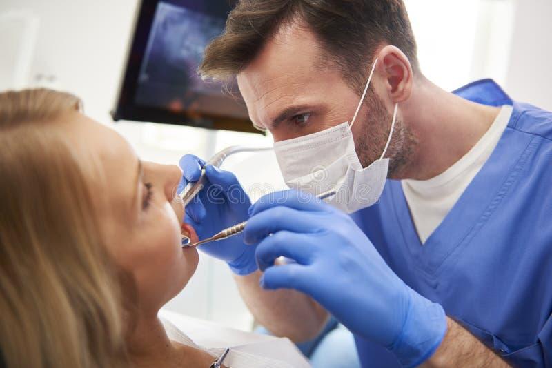 Geconcentreerde stomatologist die vrouw voor tandholte behandelen stock afbeeldingen