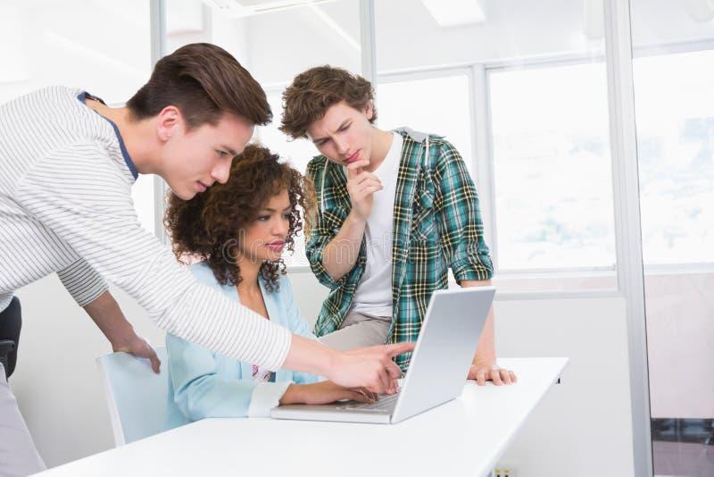 Geconcentreerde studenten die aan laptop samenwerken royalty-vrije stock foto's