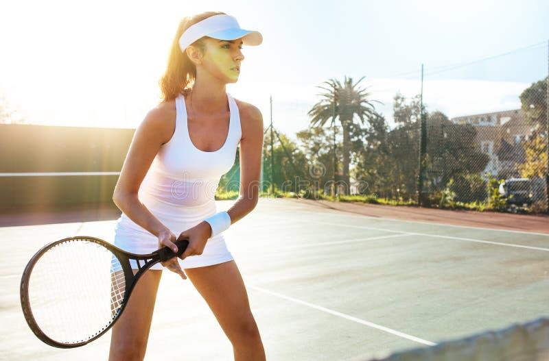 Geconcentreerde tennisspeler klaar voor gelijke op een zonnige dag stock fotografie