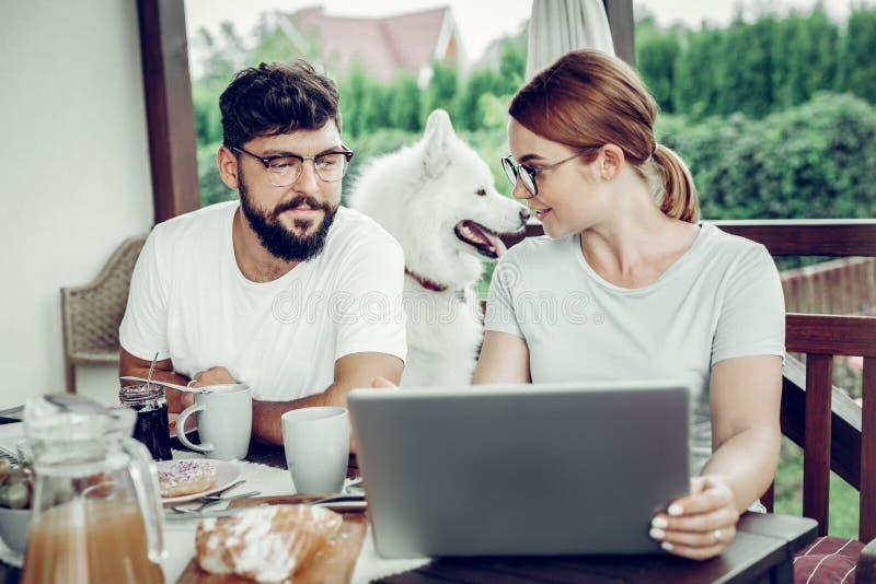 Geconcentreerde vrouw die het werk aangaande laptop tonen aan haar echtgenoot stock foto's