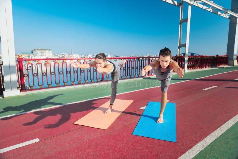 Geconcentreerde vrouw en trainer die met yoga mediteren stock afbeeldingen