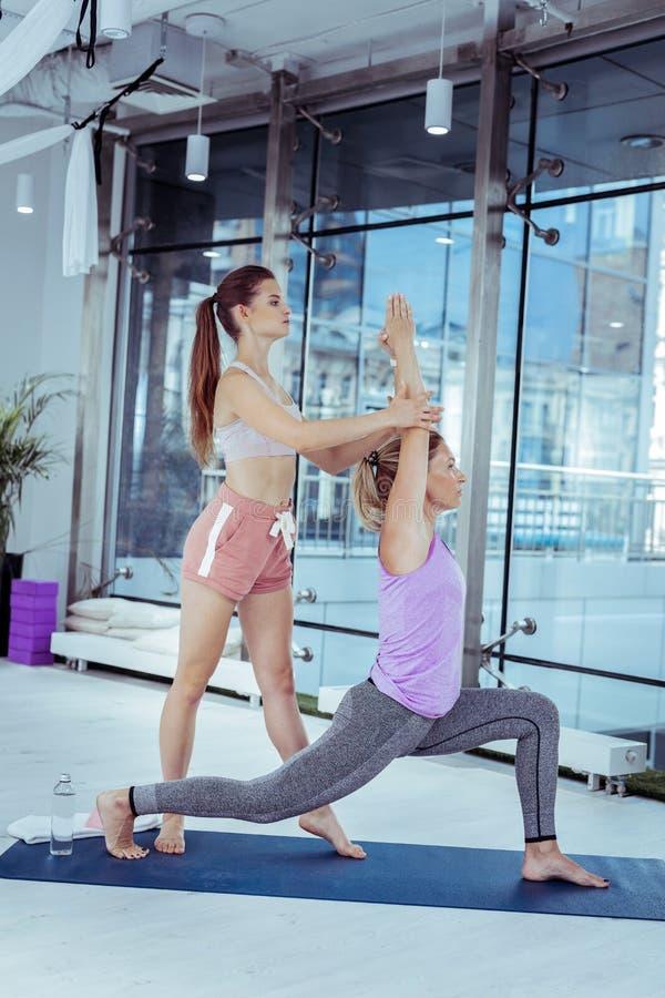 Geconcentreerde vrouwelijke trainer bewegende vrouw tijdens yoga royalty-vrije stock afbeeldingen