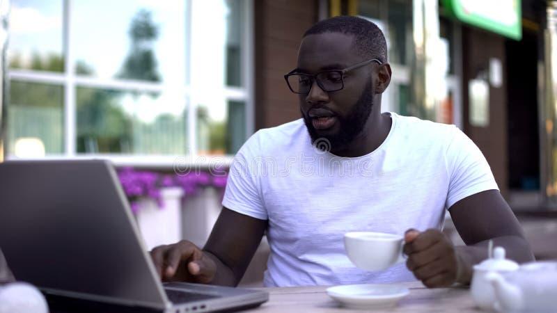 Geconcentreerde zakenman die aan laptop werken en koffiekop in bezige koffie houden, stock afbeelding