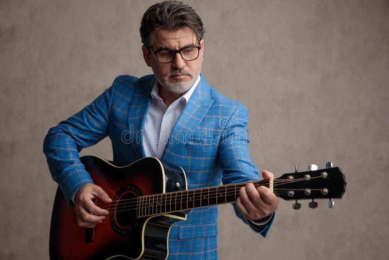 Geconcentreerde zakenman die akoestische gitaar spelen terwijl het dragen van een blauw kostuum stock foto