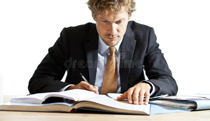 Geconcentreerde zakenman die bij bureau werken stock afbeeldingen