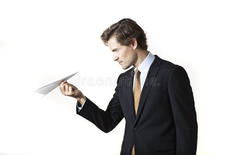 Geconcentreerde zakenman die document vliegtuig bekijken stock afbeeldingen