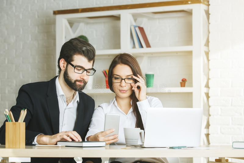 Geconcentreerde zakenman en vrouw die smartphone gebruiken stock afbeelding