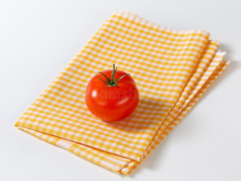 Gecontroleerde theedoek en rode tomaat royalty-vrije stock afbeeldingen