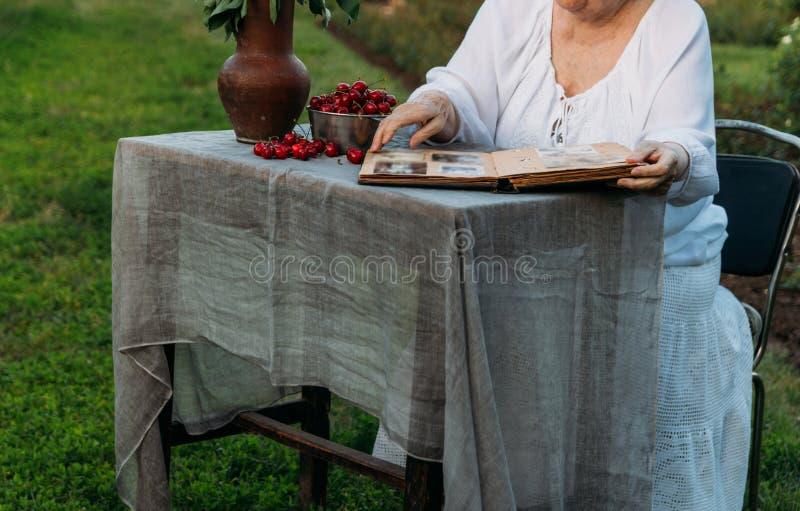 Gedächtnisse der älteren Personen Besuchsgroßmutter Großmutter, die in einem Stuhl im Garten sitzt und ein altes Album mit Fotos, lizenzfreie stockfotografie