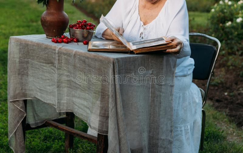 Gedächtnisse der älteren Personen Besuchsgroßmutter Großmutter, die in einem Stuhl im Garten sitzt und ein altes Album mit Fotos, stockbild