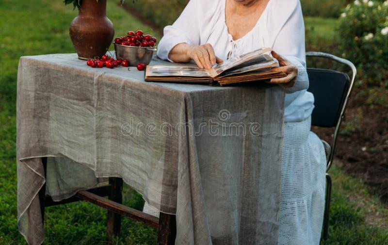 Gedächtnisse der älteren Personen Besuchsgroßmutter Großmutter, die in einem Stuhl im Garten sitzt und ein altes Album mit Fotos, stockfoto