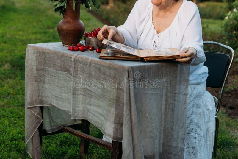 Gedächtnisse der älteren Personen Besuchsgroßmutter Großmutter, die in einem Stuhl im Garten sitzt und ein altes Album mit Fotos, stockfotos