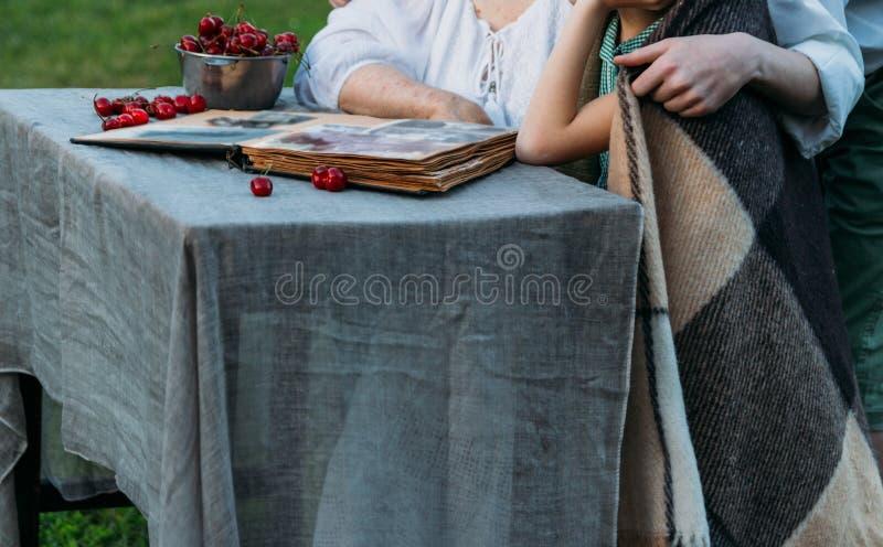 Gedächtnisse der älteren Personen Besuchsgroßmutter Großmutter mit ihren Enkelkindern, die in einem Stuhl im Garten sitzen und ei stockfotos