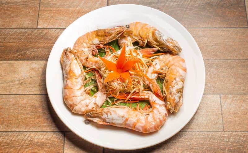 Gedämpfte Meeresfrüchte oder gedämpfte Garnele mit Kräutern und Gemüse im weißen Teller auf hölzerner Tabelle lizenzfreie stockbilder