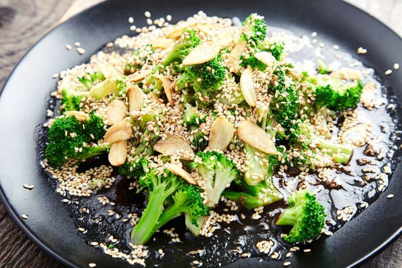 Gedämpfter Brokkoli mit Knoblauchchips und Samen des indischen Sesams lizenzfreie stockfotos
