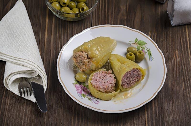 Gedämpfter grüner Paprika angefüllt mit Fleisch auf einem hölzernen Hintergrund, mit Oliven und Salz in einer Flasche, Draufsicht lizenzfreie stockfotografie
