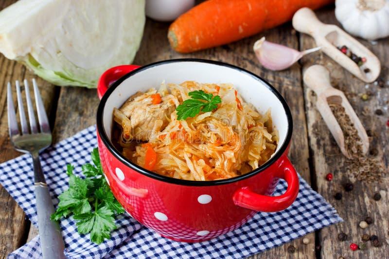 Gedämpfter Kohl mit Fleisch, Gemüse und Gewürzen auf Holztisch stockfotos
