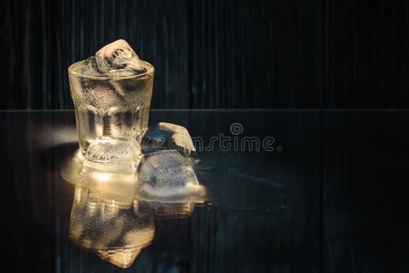 gedämpftes Glas mit kaltem Wodka oder Rum oder Tequila und Eis mit Reflexion auf einem Glastisch auf einem schwarzen hölzernen Hi lizenzfreies stockfoto